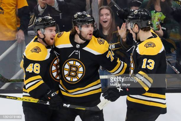 Jake DeBrusk of the Boston Bruins celebrates with Matt Grzelcyk and Charlie Coyle after scoring a goal against the Vegas Golden Knights during the...
