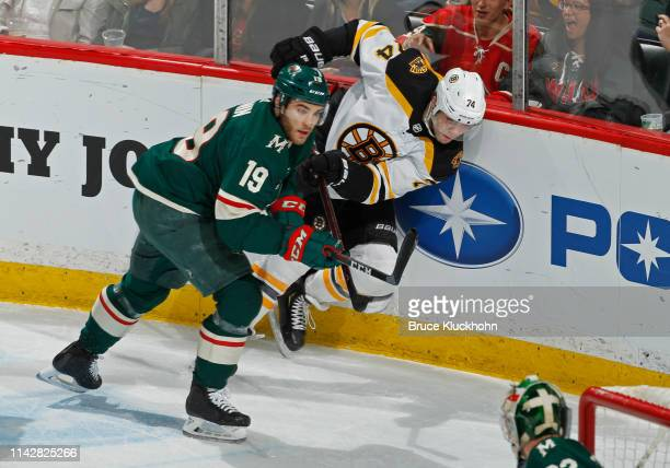 Jake DeBrusk of the Boston Bruins clears the puck as Luke Kunin of the Minnesota Wild defends during a game at Xcel Energy Center on April 4, 2019 in...
