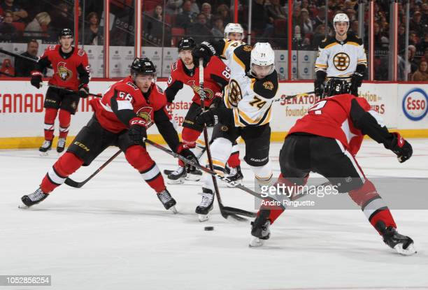 Jake DeBrusk of the Boston Bruins controls the puck against Maxime Lajoie and Dylan DeMelo of the Ottawa Senators at Canadian Tire Centre on October...