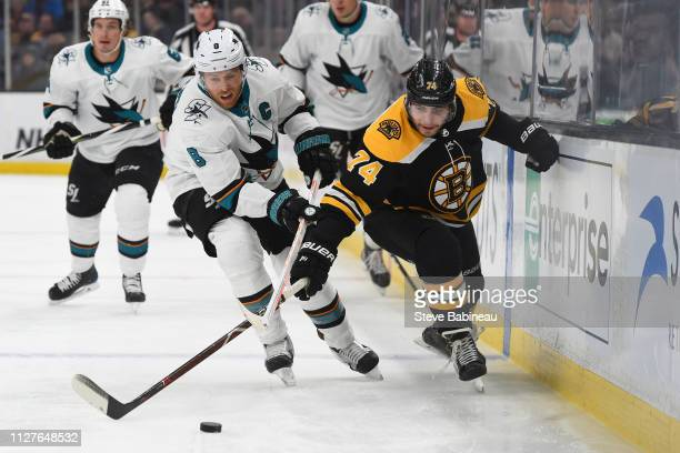 Jake DeBrusk of the Boston Bruins reaches for the puck against Joe Pavelski of the San Jose Sharks at the TD Garden on February 26 2019 in Boston...