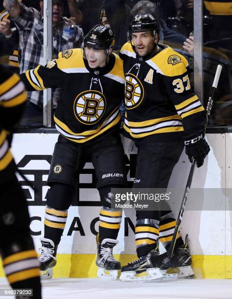 Jake DeBrusk of the Boston Bruins right celebrates with Patrice Bergeron after scoring a goal against the Toronto Maple Leafs during the first period...