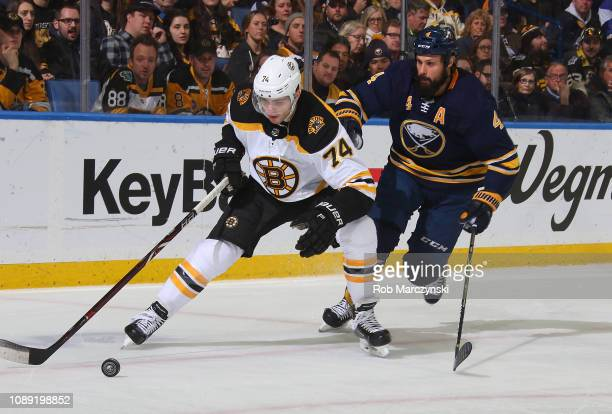 Jake DeBrusk of the Boston Bruins skates against Zach Bogosian of the Buffalo Sabres during an NHL game on December 29 2018 at KeyBank Center in...