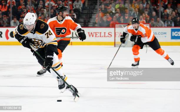 Jake DeBrusk of the Boston Bruins skates the puck against Matt Niskanen and Joel Farabee of the Philadelphia Flyers on March 10 2020 at the Wells...