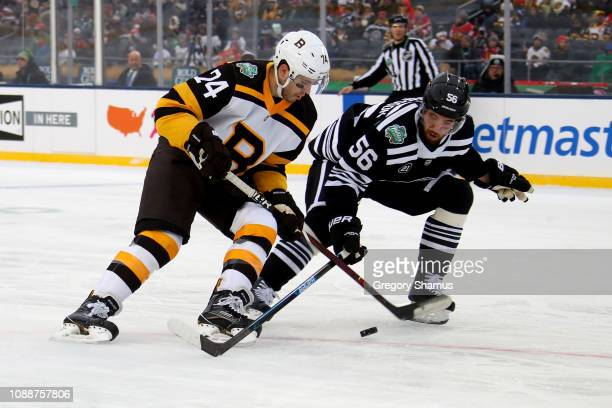 Jake DeBrusk of the Boston Bruins skates with the puck while being pursued by Erik Gustafsson of the Chicago Blackhawks in the second period during...