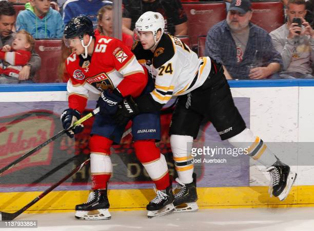 Jake DeBrusk of the Boston Bruins ties up Mackenzie Weegar of the Florida Panthers along the boards during third period action at the BBT Center on...