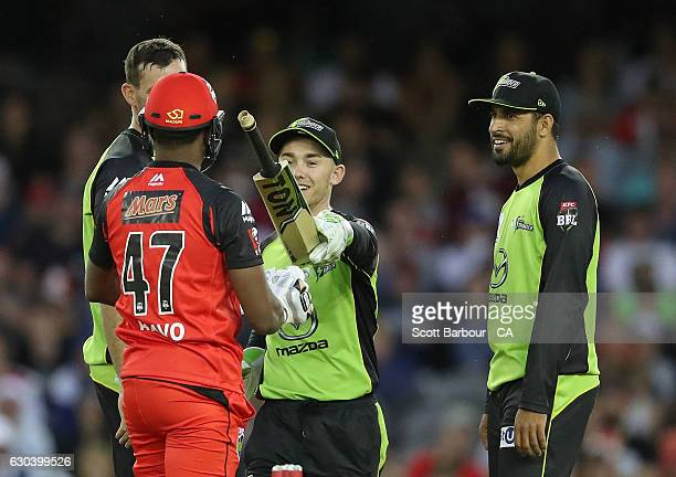 Jake Doran of the Thunder hands back the bat to Dwayne Bravo of the Renegades after he lost grip of his bat after being bowled out during the Big...