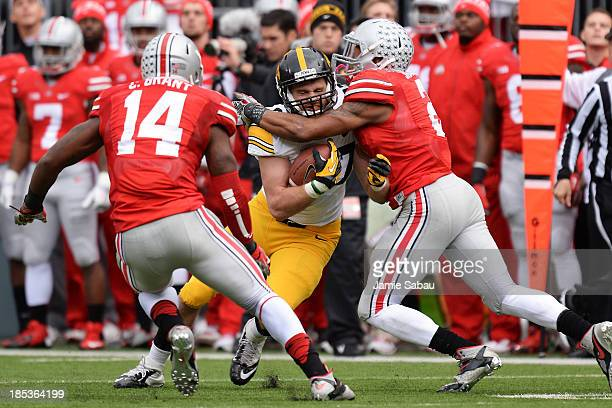 Jake Duzey of the Iowa Hawkeyes is wrapped up by Ryan Shazier of the Ohio State Buckeyes in the second quarter at Ohio Stadium on October 19 2013 in...