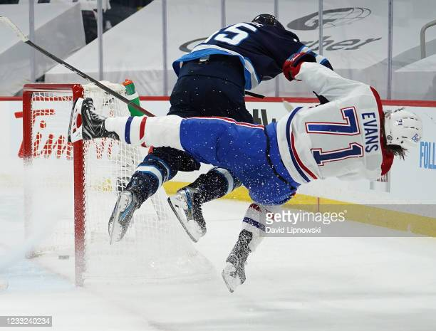 Jake Evans of the Montreal Canadiens is checked hard by Mark Scheifele of the Winnipeg Jets after Evans's third-period empty-net goal in Game One of...