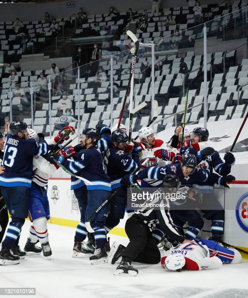 Jake Evans of the Montreal Canadiens is left injured after scoring a third period empty net goal and then checked hard by Mark Scheifele of the...