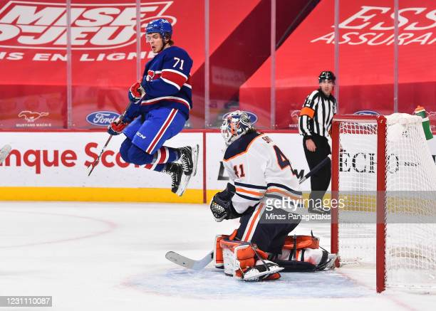 Jake Evans of the Montreal Canadiens jumps in the air in front of goaltender Mike Smith of the Edmonton Oilers during the second period at the Bell...