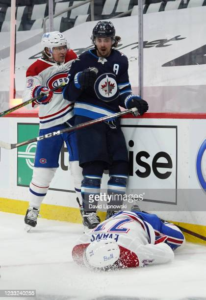 Jake Evans of the Montreal Canadiens lies on the ice injured from a hard check by Mark Scheifele of the Winnipeg Jets after Evans's third-period...