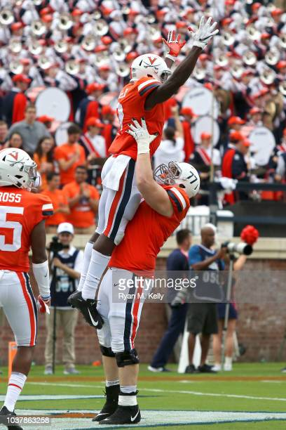 Jake Fieler of the Virginia Cavaliers lifts teammate Joe Reed in celebration after scoring a touchdown in the second half during a game against the...