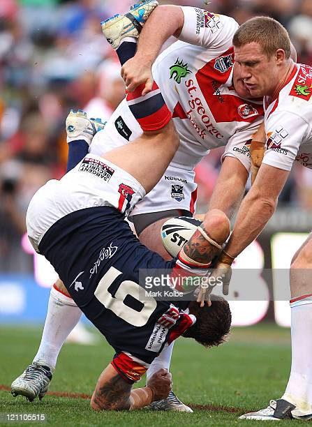 Jake Friend of the Roosters is tackled by Michael Weyman of the Dragons during the round 23 NRL match between the St George Illawarra Dragons and the...