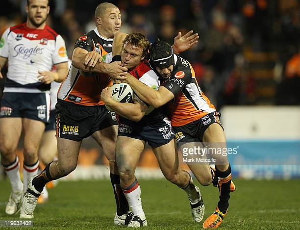 Jake Friend of the Roosters is tackled during the round 20 NRL match between the Wests Tigers and the Sydney Roosters at Leichhardt Oval on July 23...
