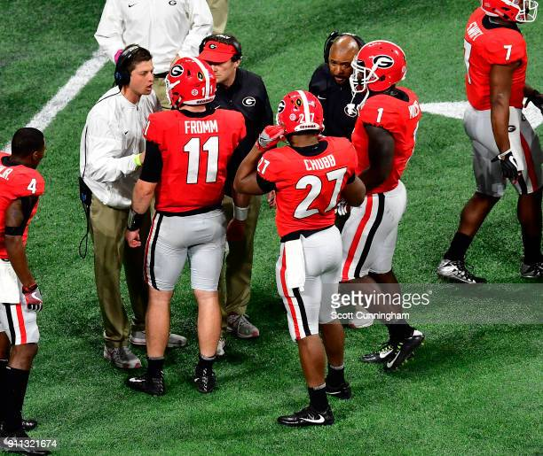 Jake Fromm Nick Chubb and Sony Michel of the Georgia Bulldogs speak with coaches during a timeout against the Alabama Crimson Tide in the CFP...