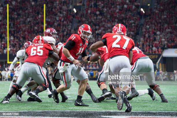 Jake Fromm of the Georgia Bulldogs hands the ball off to Nick Chubb against the Alabama Crimson Tide during the College Football Playoff National...