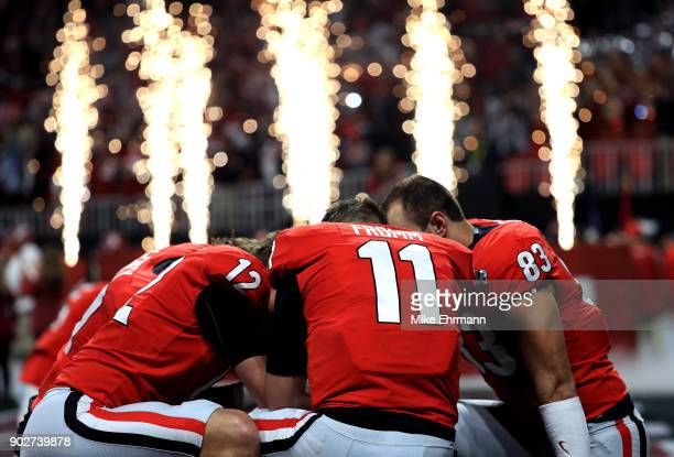 Jake Fromm of the Georgia Bulldogs huddles with his teammates before the start of the game against the Alabama Crimson Tide in the CFP National...