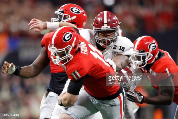 Jake Fromm of the Georgia Bulldogs is hit as he throws by Da'Ron Payne of the Alabama Crimson Tide during the first quarter in the CFP National...