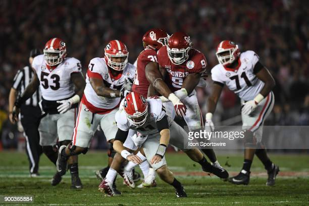 Jake Fromm of the Georgia Bulldogs is pressured by LB Kenneth Murray of the Oklahoma Sooners and DE/LB Ogbonnia Okoronkwo of the Oklahoma Sooners...