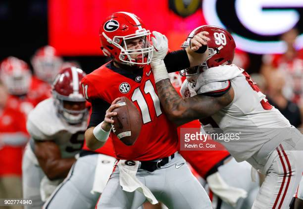 Jake Fromm of the Georgia Bulldogs is sacked by Raekwon Davis of the Alabama Crimson Tide during the second half in the CFP National Championship...