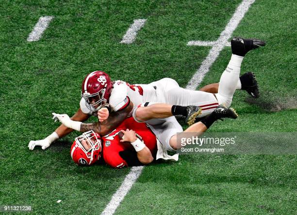 Jake Fromm of the Georgia Bulldogs is sacked by Raekwon Davis of the Alabama Crimson Tide in the CFP National Championship presented by ATT at...