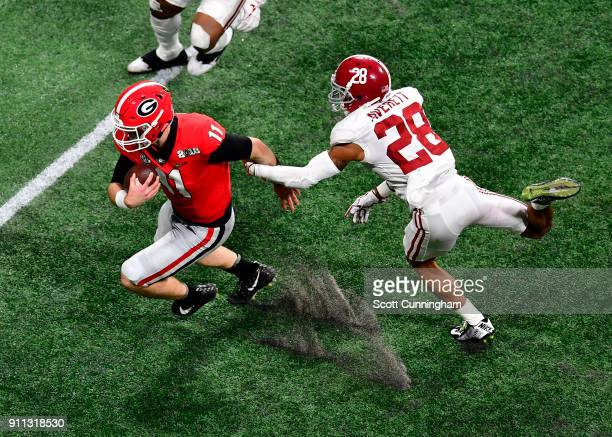 Jake Fromm of the Georgia Bulldogs is tackled by Anthony Averett of the Alabama Crimson Tide in the CFP National Championship presented by ATT at...