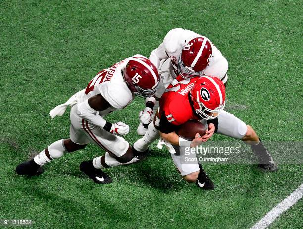 Jake Fromm of the Georgia Bulldogs is tackled by Ronnie Harrison and Mack Wilson of the Alabama Crimson Tide in the CFP National Championship...