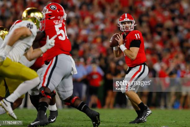 Jake Fromm of the Georgia Bulldogs looks to make a second quarter pass while playing the Notre Dame Fighting Irish at Sanford Stadium on September 21...