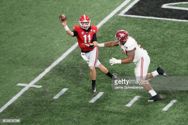 Jake Fromm of the Georgia Bulldogs passes while under pressure by Da'Ron Payne of the Alabama Crimson Tide during the College Football Playoff...