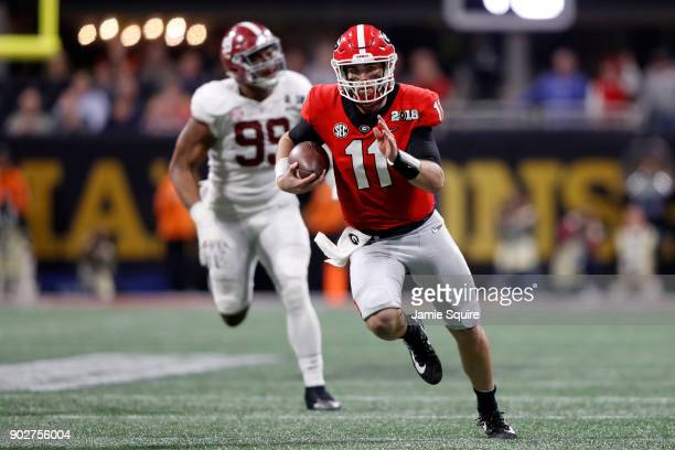Jake Fromm of the Georgia Bulldogs runs the ball during the second quarter against the Alabama Crimson Tide in the CFP National Championship...