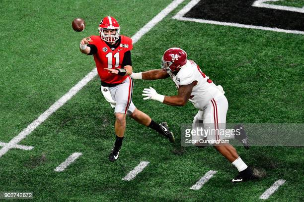 Jake Fromm of the Georgia Bulldogs throws a pass under pressure from Da'Ron Payne of the Alabama Crimson Tide during the first quarter in the CFP...