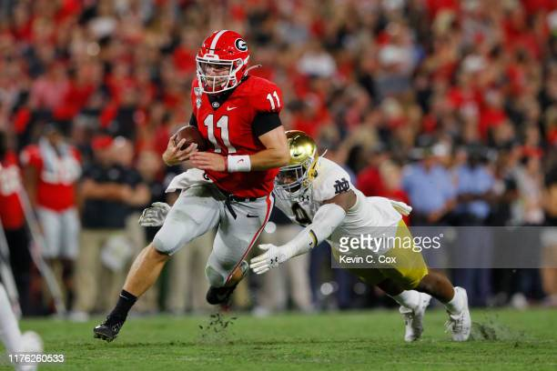 Jake Fromm of the Georgia Bulldogs tires to outrun the tackle by Lewis Cine of the Georgia Bulldogs during the second half at Sanford Stadium on...