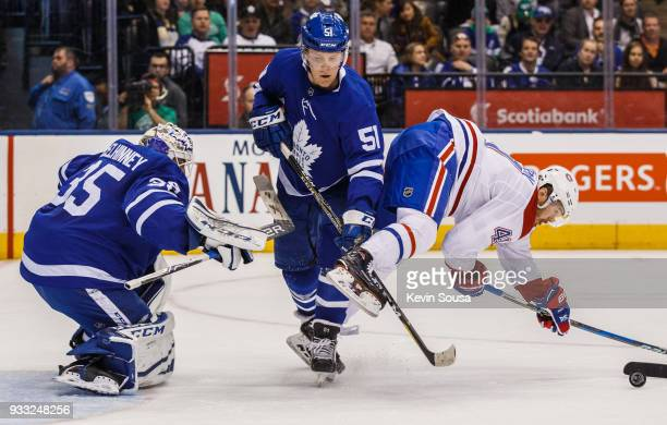 Jake Gardiner of the Toronto Maple Leafs battles with Paul Byron of the Montreal Canadiens in front of Curtis McElhinney of the Toronto Maple Leafs...