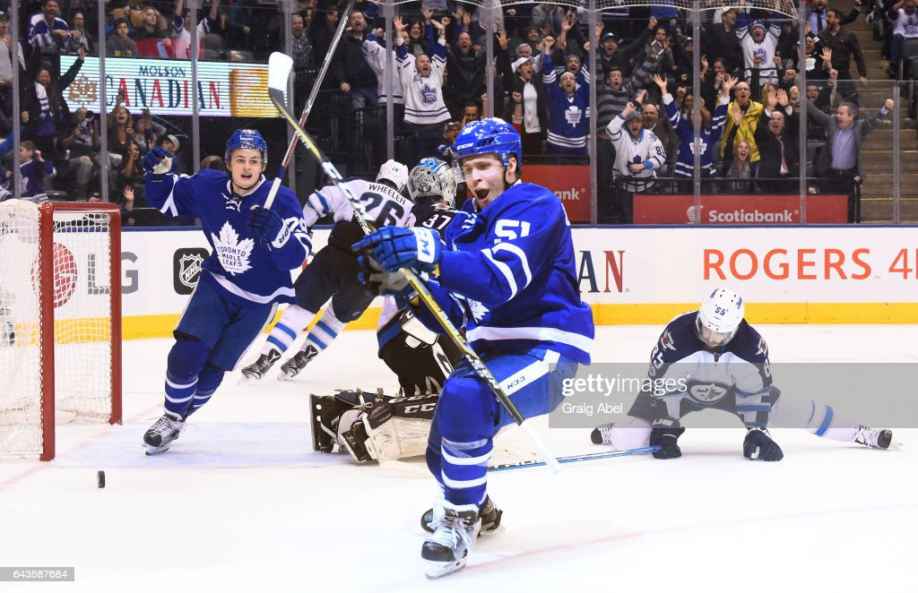Jake Gardiner #51 of the Toronto Maple Leafs celebrates his game winning overtime goal against Connor Hellebuyck #37 of the Winnipeg Jets with teammate William Nylander #29 at the Air Canada Centre on February 21, 2017 in Toronto, Ontario, Canada.