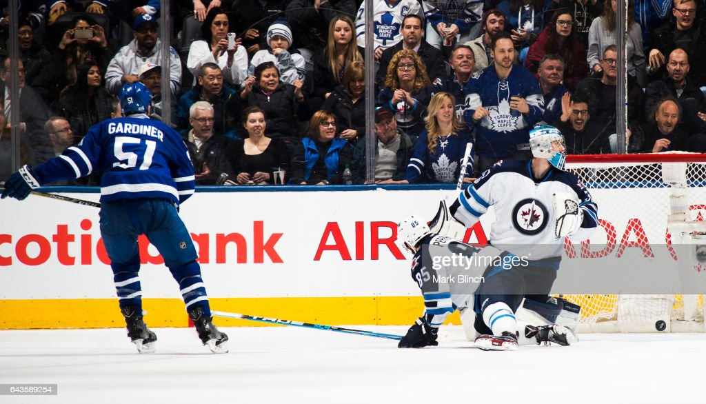 Jake Gardiner #51 of the Toronto Maple Leafs scores the game winning overtime goal on Connor Hellebuyck #37 of the Winnipeg Jets at the Air Canada Centre on February 21, 2017 in Toronto, Ontario, Canada.
