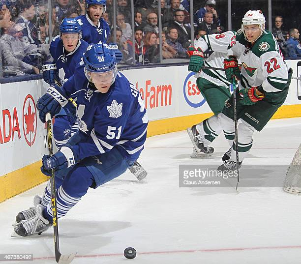Jake Gardiner of the Toronto Maple Leafs tries to clear a puck against the Minnesota Wild during an NHL game at the Air Canada Centre on March 23...