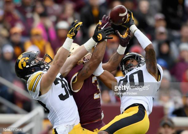 Jake Gervase and Julius Brents of the Iowa Hawkeyes break up a pass intended for Chris AutmanBell of the Minnesota Golden Gophers during the second...