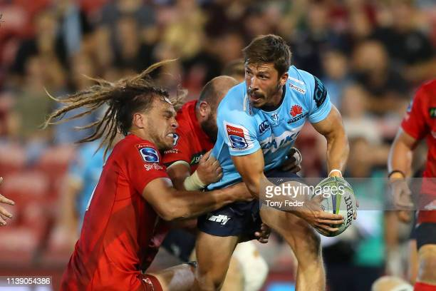 Jake Gordon of the Waratahs is tackled during the round seven Super Rugby match between the Waratahs and the Sunwolves at McDonald Jones Stadium on...