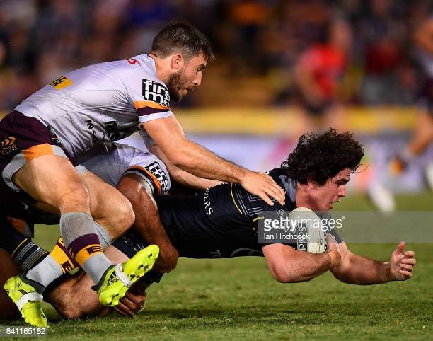 Jake Granville of the Cowboys is tackled by Ben Hunt of the Broncos during the round 26 NRL match between the North Queensland Cowboys and the...