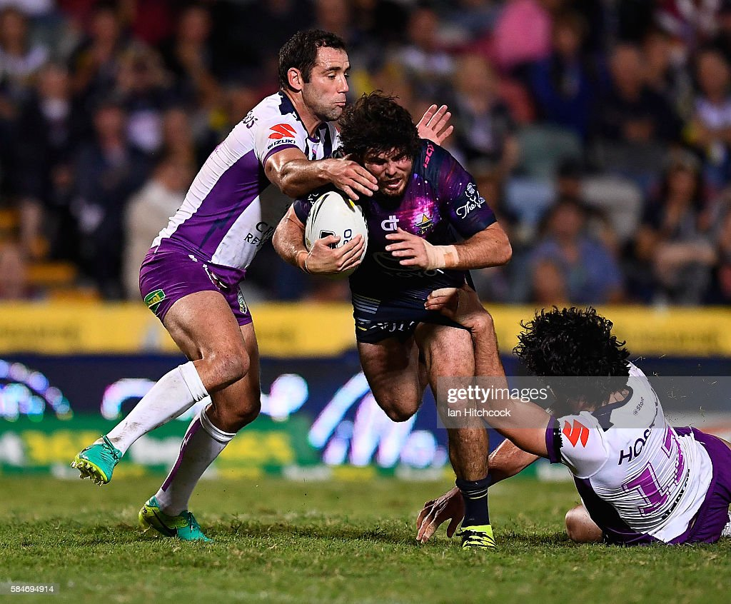 Jake Granville of the Cowboys is tackled by Cameron Smith and Tohu Harris of the Storm during the round 21 NRL match between the North Queensland Cowboys and the Melbourne Storm at 1300SMILES Stadium on July 30, 2016 in Townsville, Australia.