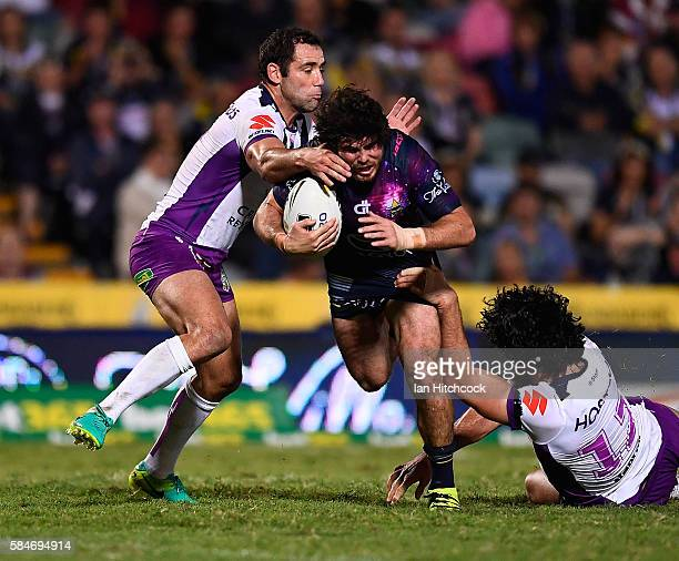Jake Granville of the Cowboys is tackled by Cameron Smith and Tohu Harris of the Storm during the round 21 NRL match between the North Queensland...