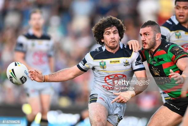 Jake Granville of the Cowboys passes the ball despite the oncoming tackle of Robbie Farah of the Rabbitohs during the round 19 NRL match between the...