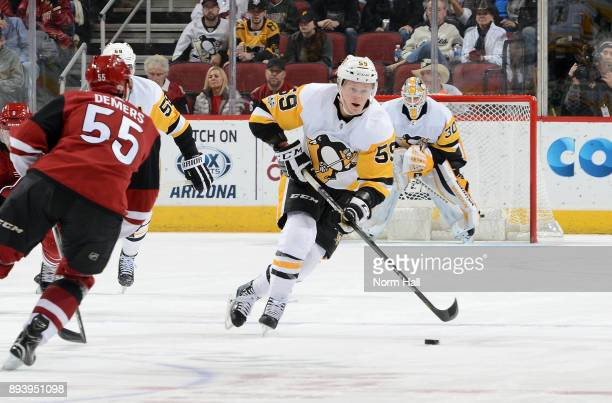 Jake Guentzel of the Pittsburgh Penguins advances the puck up ice in front of Jason Demers of the Arizona Coyotes during the first period at Gila...