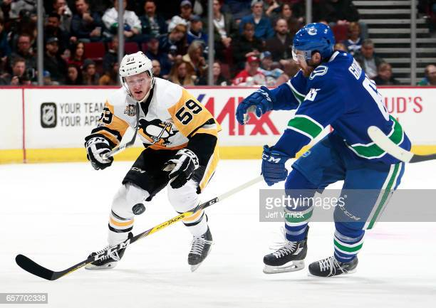 Jake Guentzel of the Pittsburgh Penguins and Alexandre Grenier of the Vancouver Canucks watch a loose puck during their NHL game at Rogers Arena...