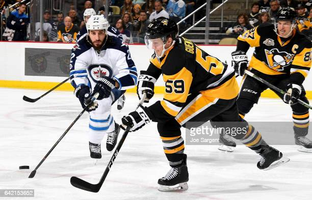 Jake Guentzel of the Pittsburgh Penguins and Chris Thorburn of the Winnipeg Jets play the puck at PPG Paints Arena on February 16 2017 in Pittsburgh...