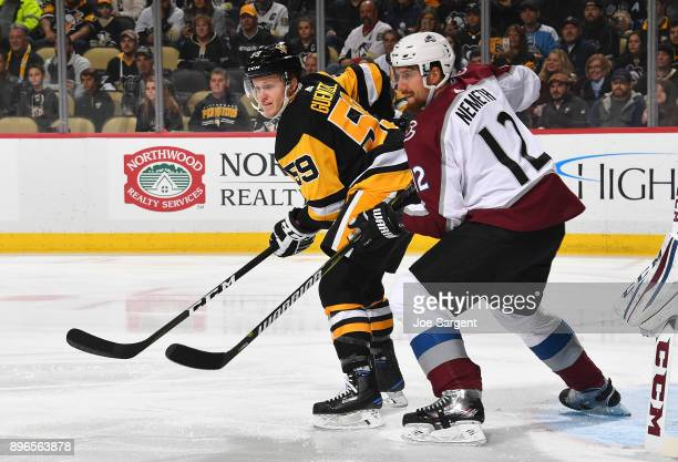 Jake Guentzel of the Pittsburgh Penguins and Patrik Nemeth of the Colorado Avalanche battle for position at PPG Paints Arena on December 11 2017 in...