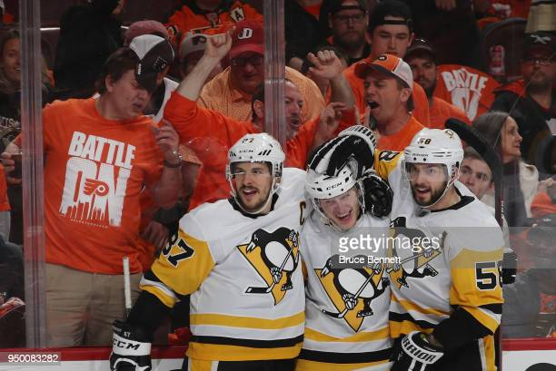 Jake Guentzel of the Pittsburgh Penguins celebrates his goal at 1258 of the third period against the Philadelphia Flyers and is joined by Sidney...