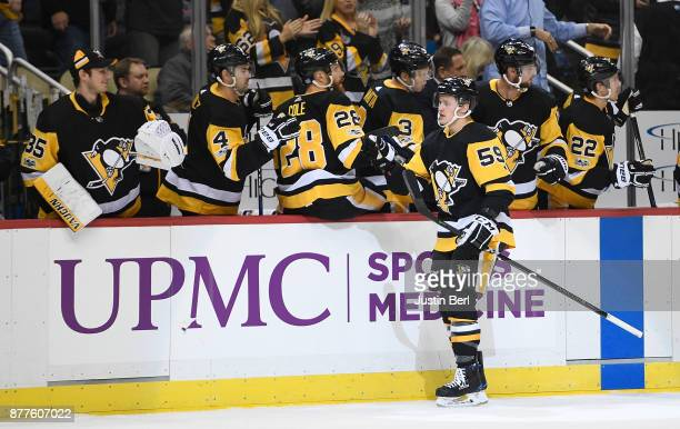Jake Guentzel of the Pittsburgh Penguins celebrates with teammates on the bench after scoring a goal in the first period during the game against the...