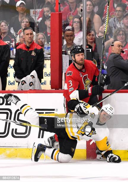 Jake Guentzel of the Pittsburgh Penguins falls to the ice after colliding with Marc Methot of the Ottawa Senators during the third period in Game...
