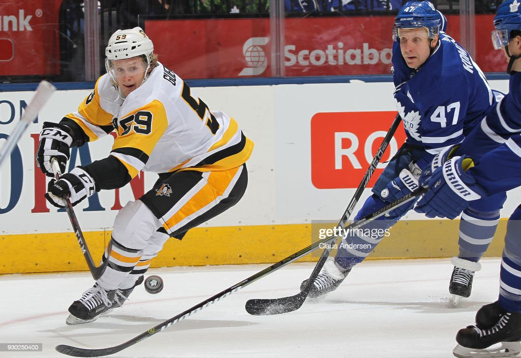 Jake Guentzel #59 of the Pittsburgh Penguins flips a puck away from a checking Leo Komarov #47 of the Toronto Maple Leafs during an NHL game at the Air Canada Centre on March 10, 2018 in Toronto, Ontario, Canada. The Maple Leafs defeated the Penguins 5-2.